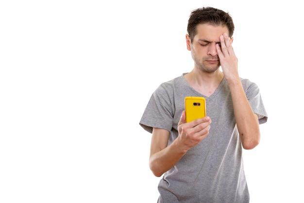 Młody człowiek za pomocą telefonu komórkowego, patrząc na stres