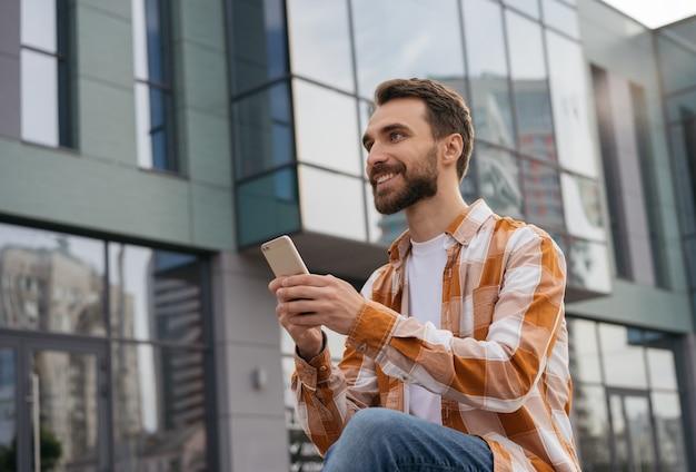 Młody człowiek za pomocą telefonu komórkowego, pracujący w trybie online, siedząc na zewnątrz