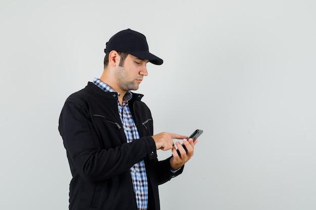 Młody człowiek za pomocą telefonu komórkowego w koszuli, kurtce, czapce i patrząc zajęty, widok z przodu.