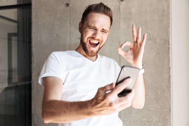 Młody człowiek za pomocą telefonu komórkowego w pomieszczeniu pokazując dobry gest.