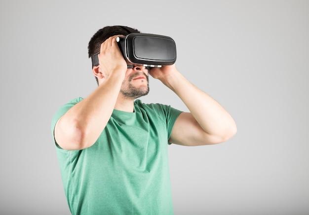 Młody człowiek za pomocą zestawu słuchawkowego wirtualnej rzeczywistości na białym tle