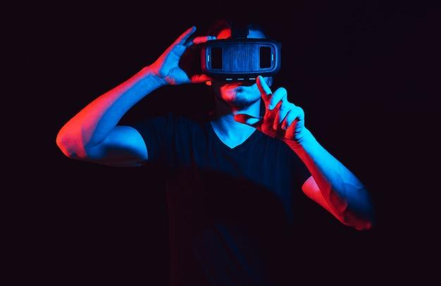 Młody człowiek za pomocą zestawu słuchawkowego wirtualnej rzeczywistości vr