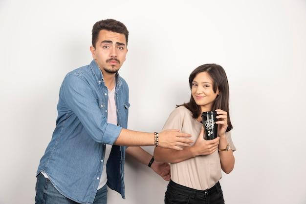 Młody człowiek zabierając dziewczynie filiżankę kawy.