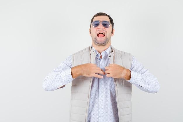 Młody człowiek zakłada okulary, próbując zamknąć suwak kurtki w beżowej kurtce i czapce i wygląda optymistycznie, widok z przodu.