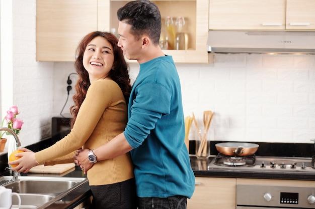 Młody człowiek zakochany przytulający swoją dziewczynę, płuczący owoce w zlewie kuchennym