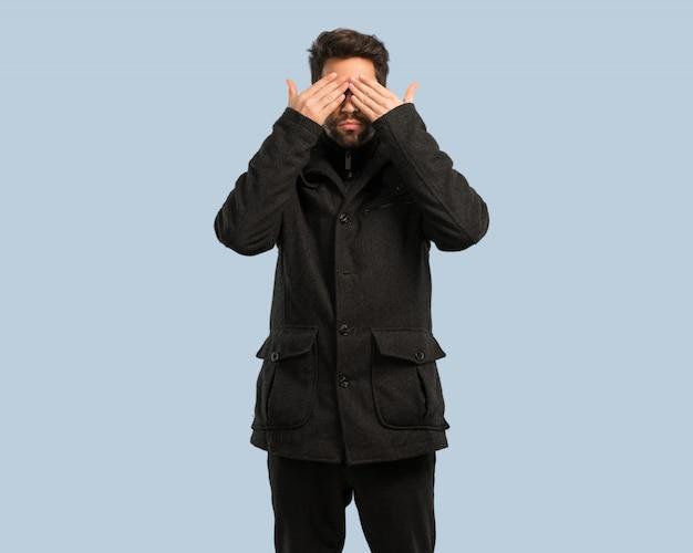 Młody człowiek zakrywa oczy