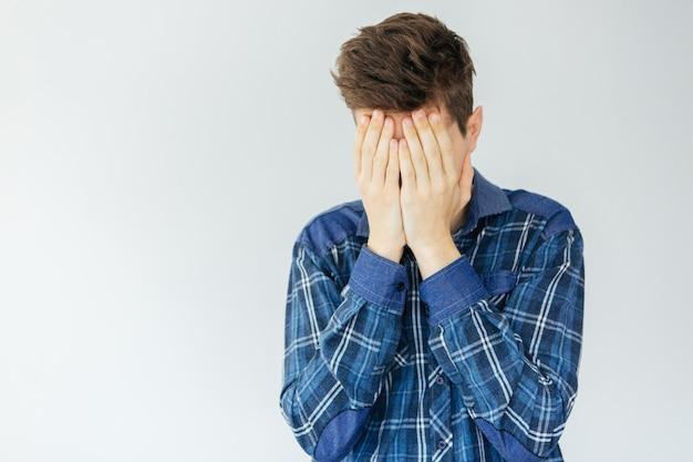 Młody człowiek zakrywa twarz dłońmi. problemy i stres. smutny mężczyzna na jasnoszarym tle