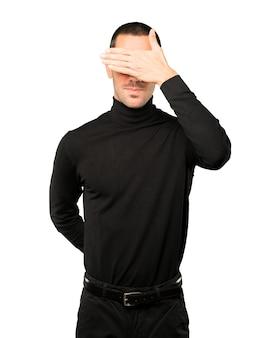 Młody człowiek zakrywający oczy rękami