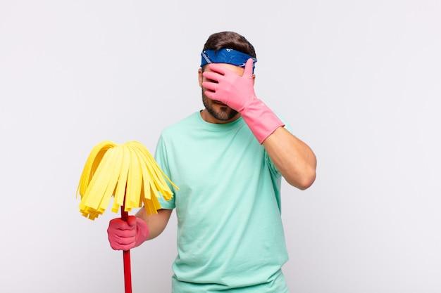Młody człowiek zakrywający twarz ręką
