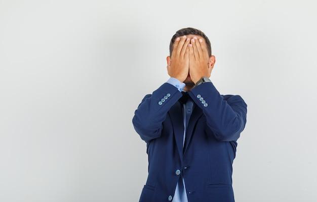 Młody człowiek zakrywający twarz rękami w garniturze i patrząc z żalem