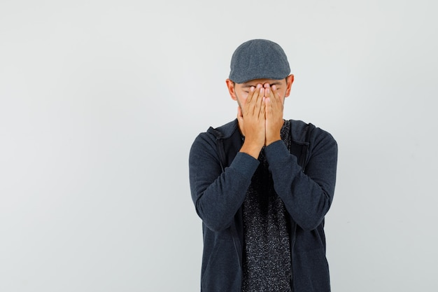 Młody człowiek zakrywający twarz rękami w t-shirt, kurtkę, czapkę i patrząc zdenerwowany, widok z przodu.