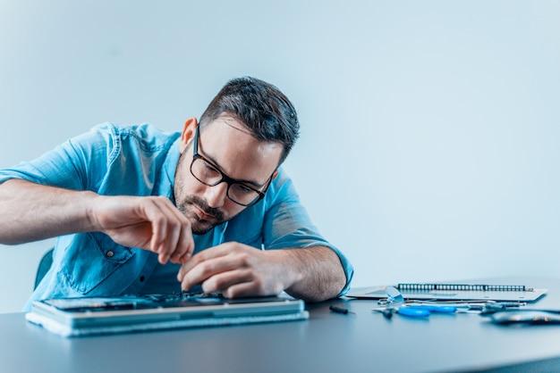 Młody człowiek załatwia łamanego laptop.