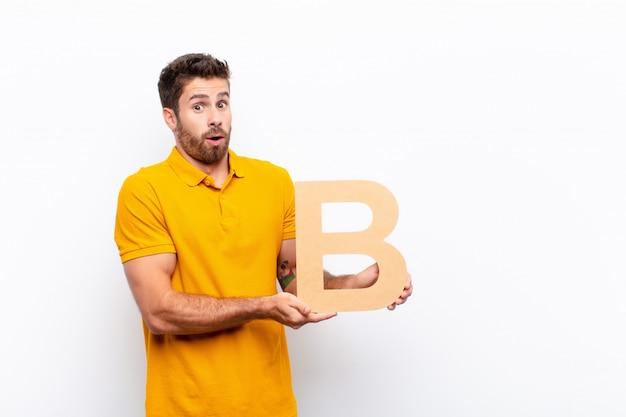 Młody człowiek zaskoczony, trzymając literę b alfabetu, aby utworzyć słowo lub zdanie