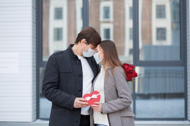 Młody człowiek zaskoczył swoją dziewczynę bukietem róż i pudełkiem w kształcie serca w mieście. walentynki. stojąc i patrząc na siebie. maska. wysokiej jakości zdjęcie