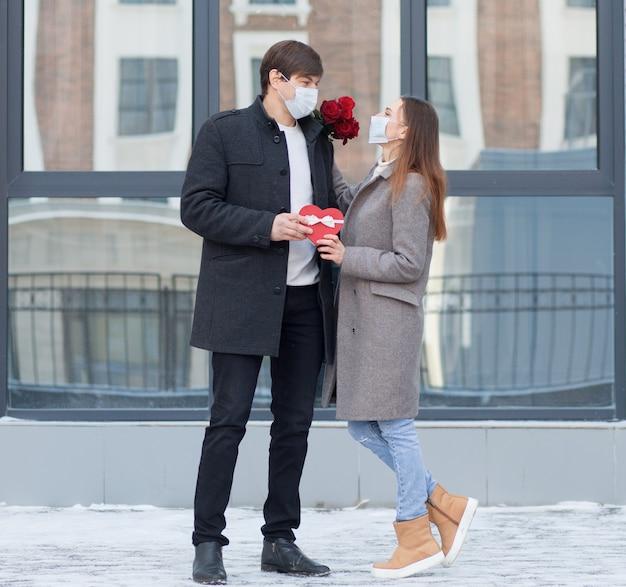 Młody człowiek zaskoczył swoją dziewczynę bukietem róż i pudełkiem w kształcie serca w mieście. walentynki. stojąc i patrząc na siebie w masce na twarz. wysokiej jakości zdjęcie