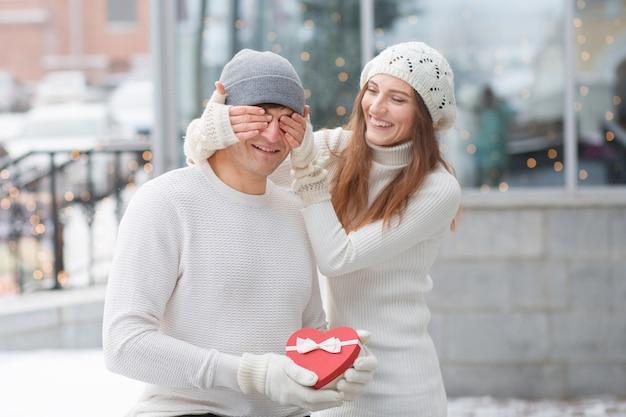 Młody człowiek zaskoczył swoją dziewczynę pudełkiem w kształcie serca w mieście