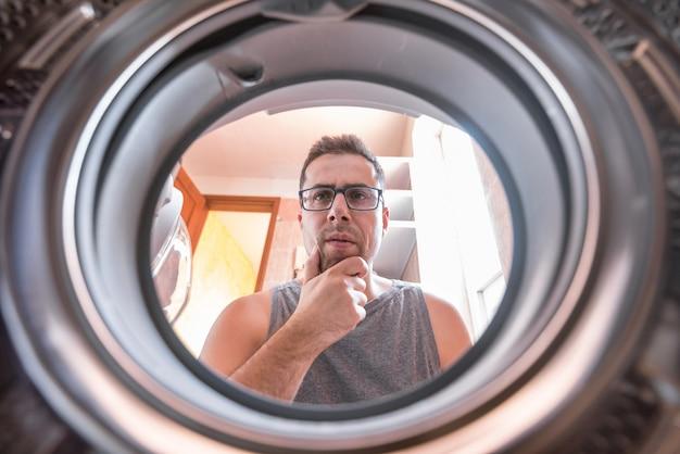Młody człowiek zastanawia się, jak działa pralka.