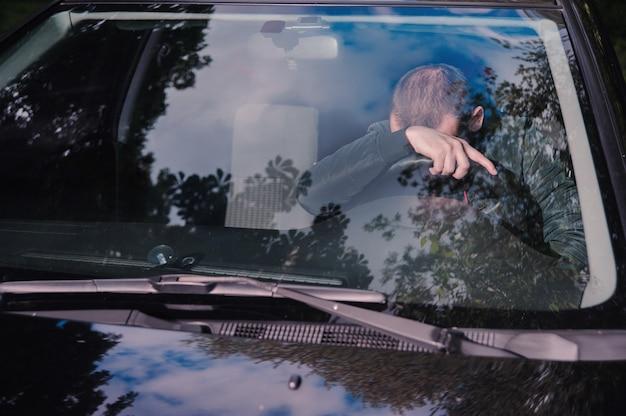 Młody człowiek zasypia w samochodzie
