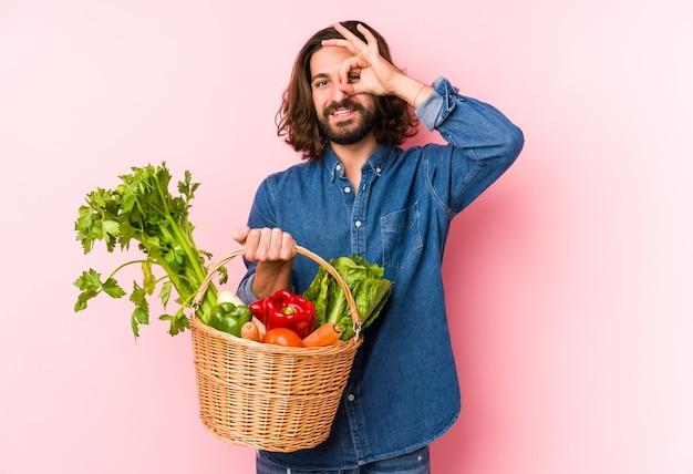 Młody człowiek zbierając organiczne warzywa z ogrodu na białym tle podekscytowany, utrzymując ok gest na oko.