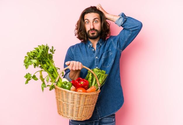 Młody człowiek, zbierając organiczne warzywa ze swojego ogrodu, jest w szoku
