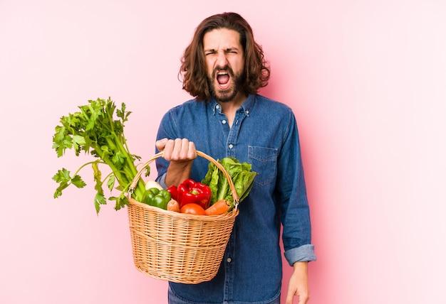 Młody człowiek zbierający organiczne warzywa z ogrodu krzyczy bardzo zły i agresywny