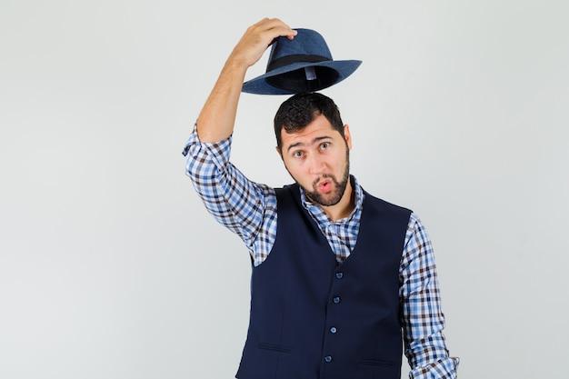 Młody człowiek zdejmując kapelusz w koszulę, kamizelkę i przystojny wygląd