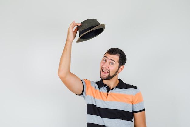 Młody człowiek zdejmując kapelusz w t-shirt i patrząc zadowolony.