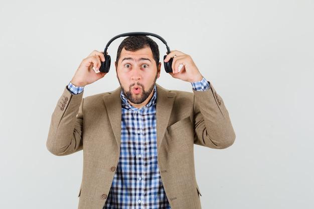 Młody człowiek zdejmujący słuchawki w koszuli, kurtce i patrząc zdziwiony