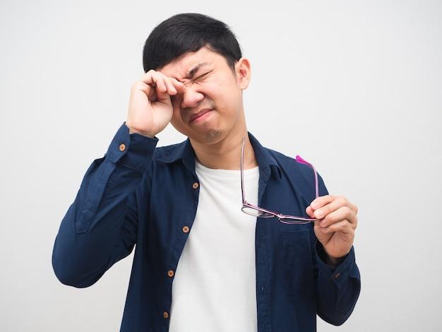Młody człowiek zdejmuje okulary i miażdży mu oko, czując się wypróbowany