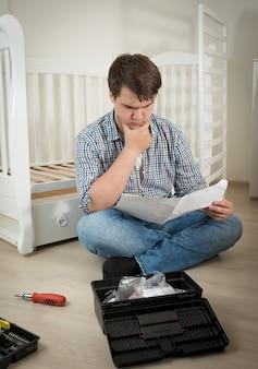 Młody człowiek zdezorientowany montażem łóżeczka dla dziecka