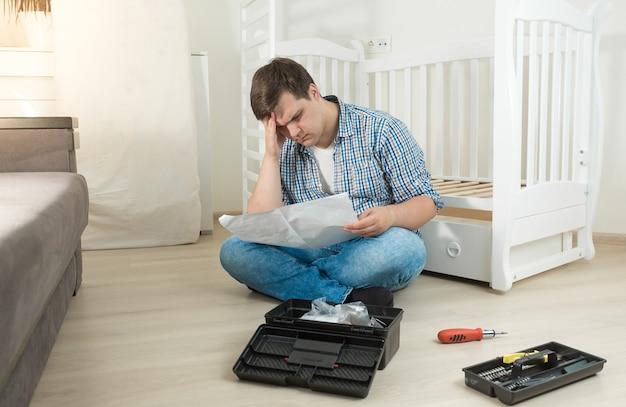 Młody człowiek zdezorientowany montażem mebli do czytania instrukcji
