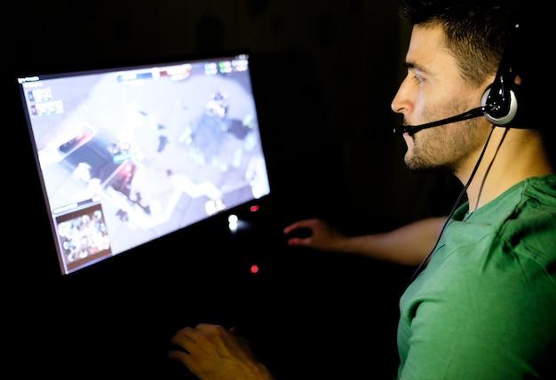 Młody człowiek ze słuchawkami, grając w gry wideo w ciemnym pokoju