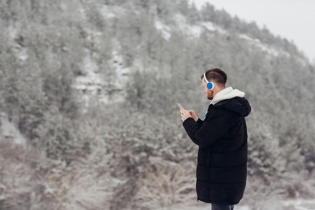 Młody człowiek ze słuchawkami korzysta z telefonu w zimowych górach na śniegu.