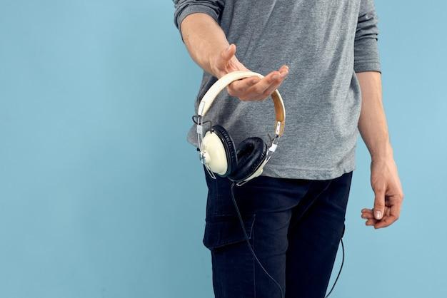 Młody człowiek ze słuchawkami na jasnoniebieskiej ścianie