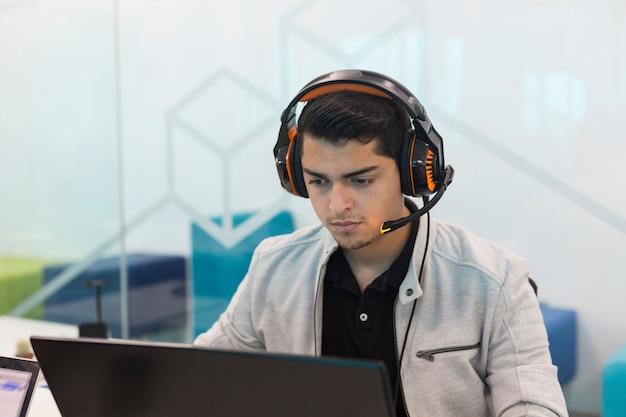 Młody człowiek ze słuchawkami, pracując na komputerze w biurze coworkingowym.