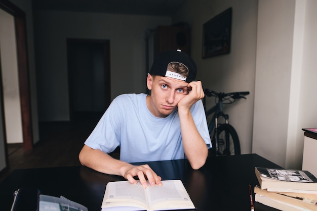 Młody człowiek ze smutnym wyrazem twarzy czyta książkę w swoim domu.