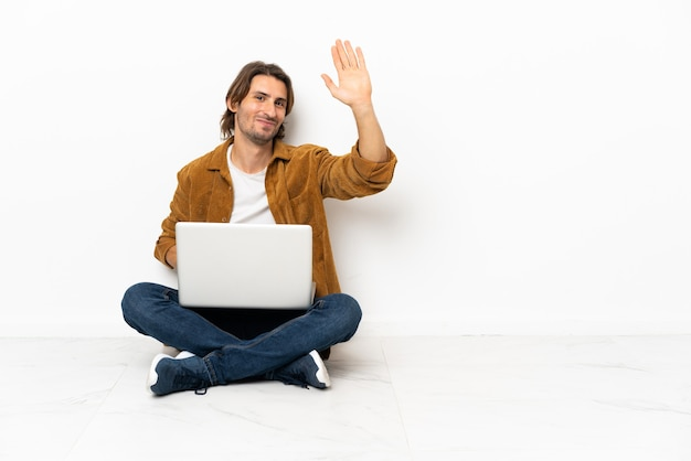 Młody człowiek ze swoim laptopem siedzi jeden na podłodze salutując ręką z happy wypowiedzi