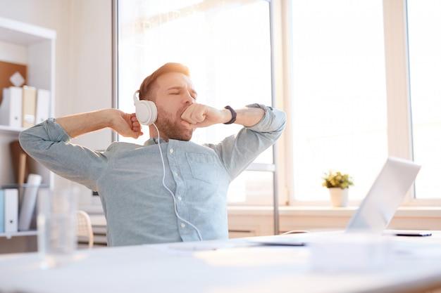 Młody człowiek ziewanie w miejscu pracy