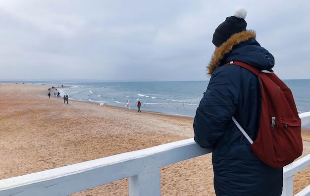 Młody człowiek zimą w kurtce, czapce i plecaku stoi na molo i patrzy na bałtyk w mieście gdańsk.