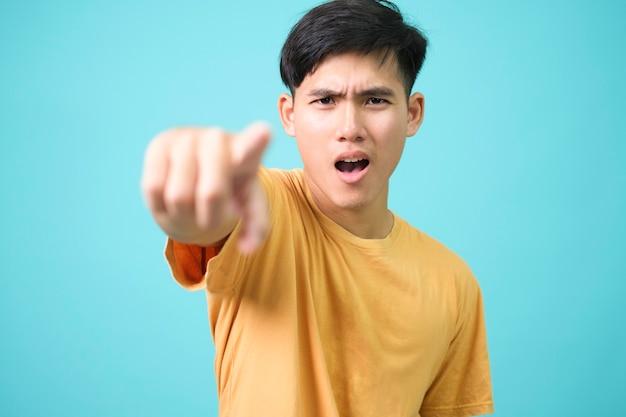 Młody człowiek zły palec wskazujący na aparat, emocje.
