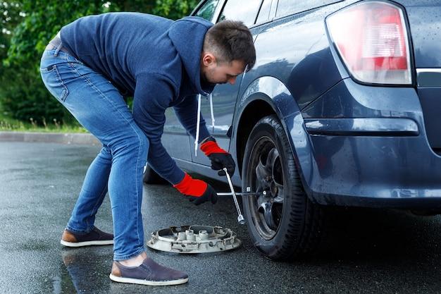 Młody człowiek zmienia gumę w swoim samochodzie po wypadku drogowym