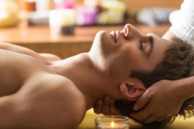 Młody człowiek zrelaksowany w spa, zbliżenie mężczyzny mającego masaż głowy