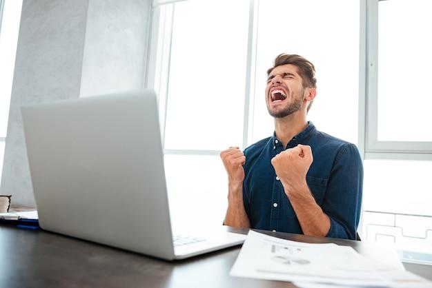 Młody człowiek zrobić gest zwycięzcy, siedząc przy stole i laptopie