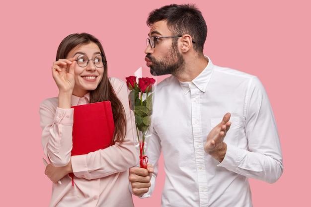 Młody czuły mężczyzna daje dziewczynie bukiet czerwonych róż, fałduje usta do pocałunku