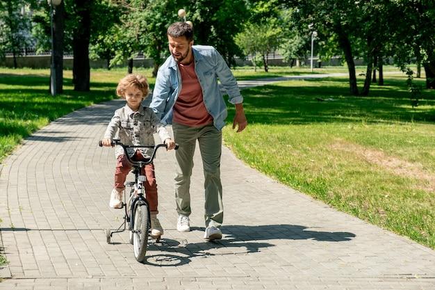 Młody czuły ojciec w codziennym stroju pomaga swojemu słodkiemu synkowi jadącemu na rowerze po drodze w publicznym parku w słoneczny letni weekend