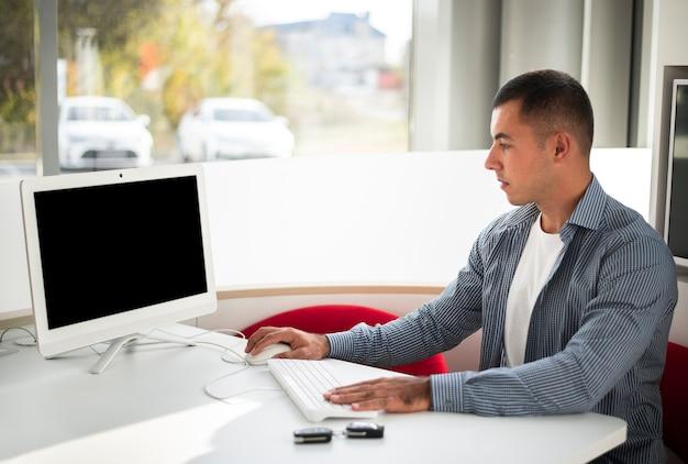Młody dealer samochodów pracuje w biurze