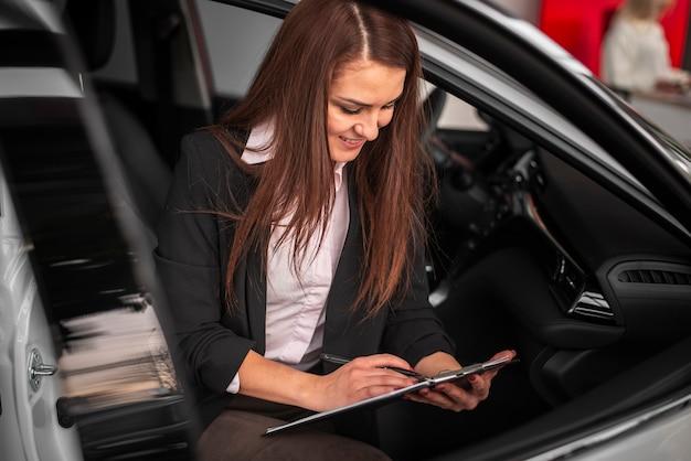 Młody dealer samochodowy podpisuje papiery samochodowe