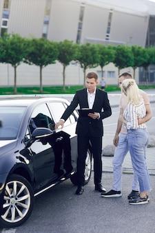 Młody dealer samochodowy w garniturze pokazuje kupującym nowy samochód. młoda para, mężczyzna i kobieta, kupują samochód. zakup maszyn, jazda próbna.