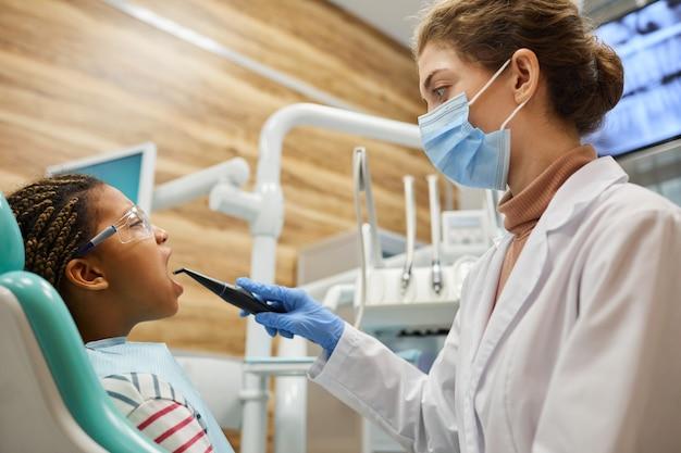 Młody dentysta w masce ochronnej pracujący z wiertarką dentystyczną, leczący zęby jej pacjenta w szpitalu