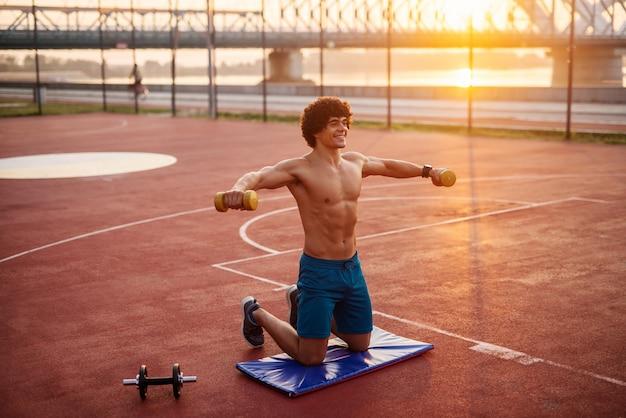 Młody, determinujący, sprawny mężczyzna, ćwiczący wcześnie rano